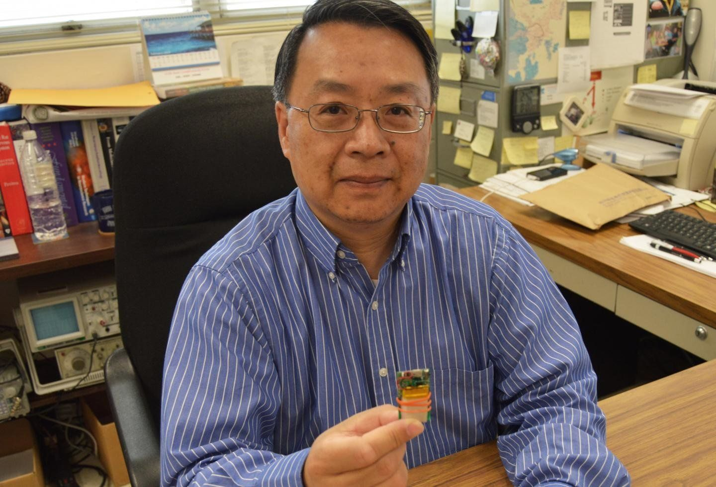 Dr.Yuan Bo Peng holding a chip that's used in the electrical stimulation method.