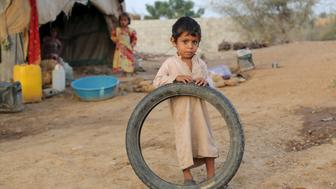 """A boy stands outside his family's hut at the Shawqaba camp for internally displaced people who were forced to leave their villages by the war in Yemen's northwestern province of Hajjah March 13, 2016. In northwest Yemen, one of the poorest countries in the Middle East, about 400 families uprooted by the war have been stuck in the Shawqaba camp in Hajjah province for the past year. Residents live in poorly built huts that protect them neither from summer heat nor winter cold in a camp that lacks the most basic services. REUTERS/Abduljabbar Zeyad SEARCH """"DISPLACED ZEYAD"""" FOR THIS STORY. SEARCH """"THE WIDER IMAGE"""" FOR ALL STORIES."""