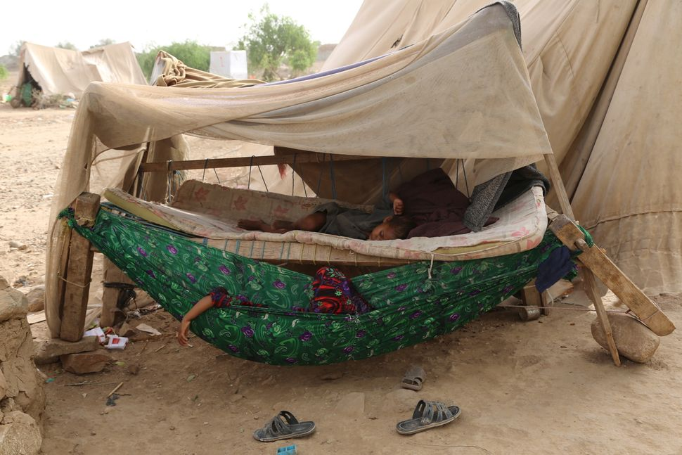 A man and a boy sleep outside a tent at the Shawqaba camp.