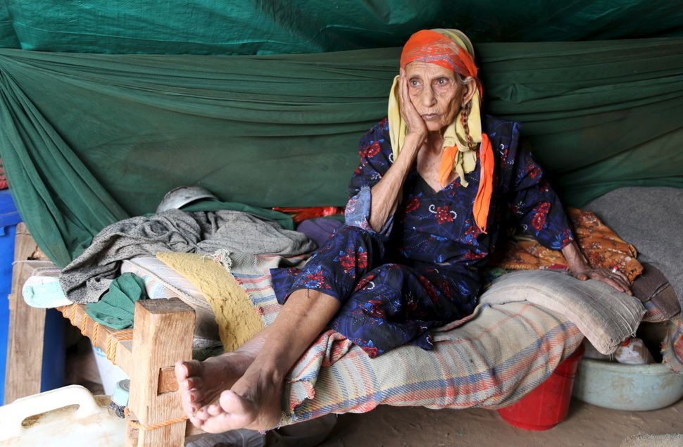 A woman sits inside her hut at the Shawqaba camp. Elderly people with health conditions complain of a lack of medic
