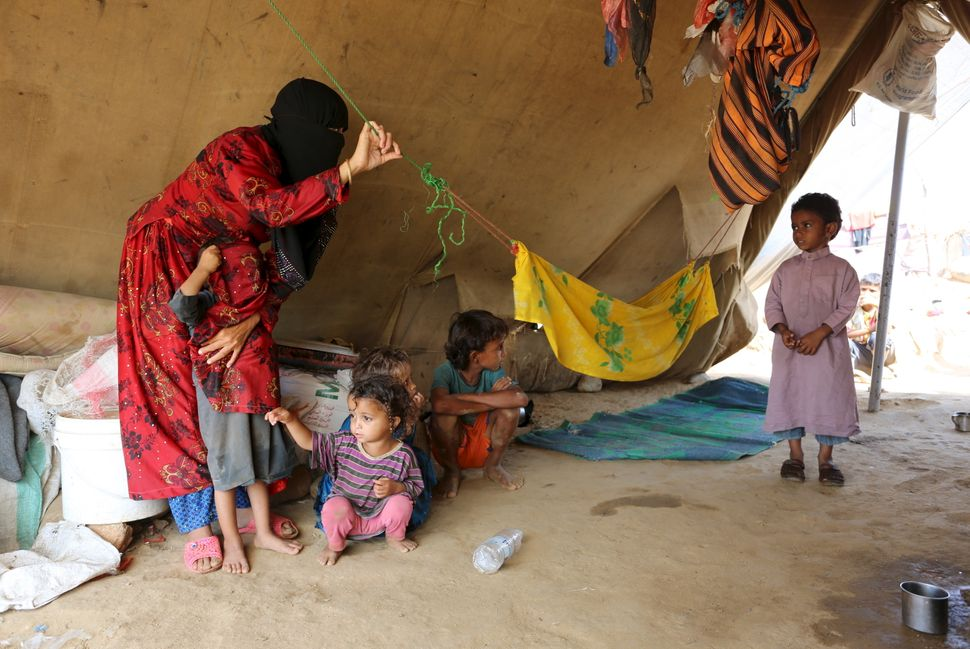 A woman and children are pictured in their tent at the Shawqaba camp.