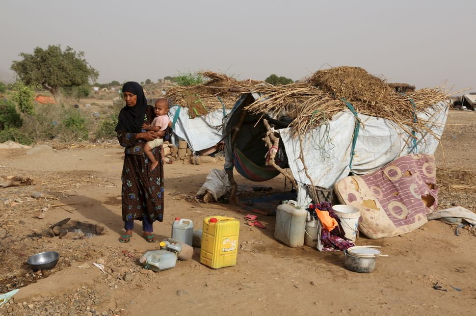 A woman carries a child at the Shawqaba camp. The residents of the camp live in poorly built huts that protect them