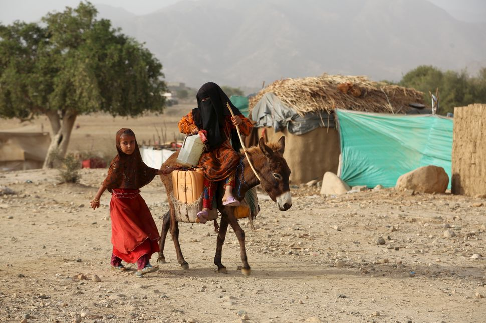 A girl rides a donkey in the camp. Many children suffer from a lack of nutrition and health services in the Shawqaba camp.