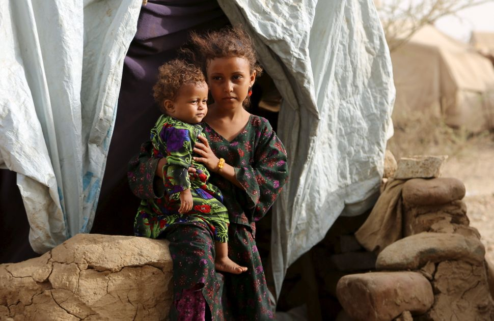 A girl holds her sister outside their family's hut. Around 400 families live in the camp.