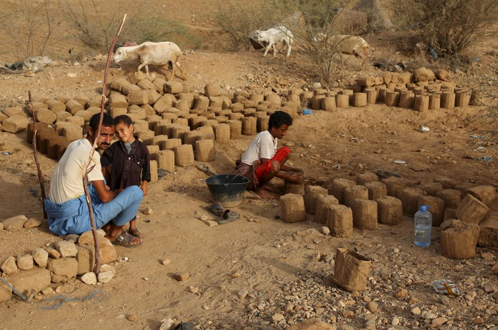 People prepare mud bricks to build a hut at the camp.