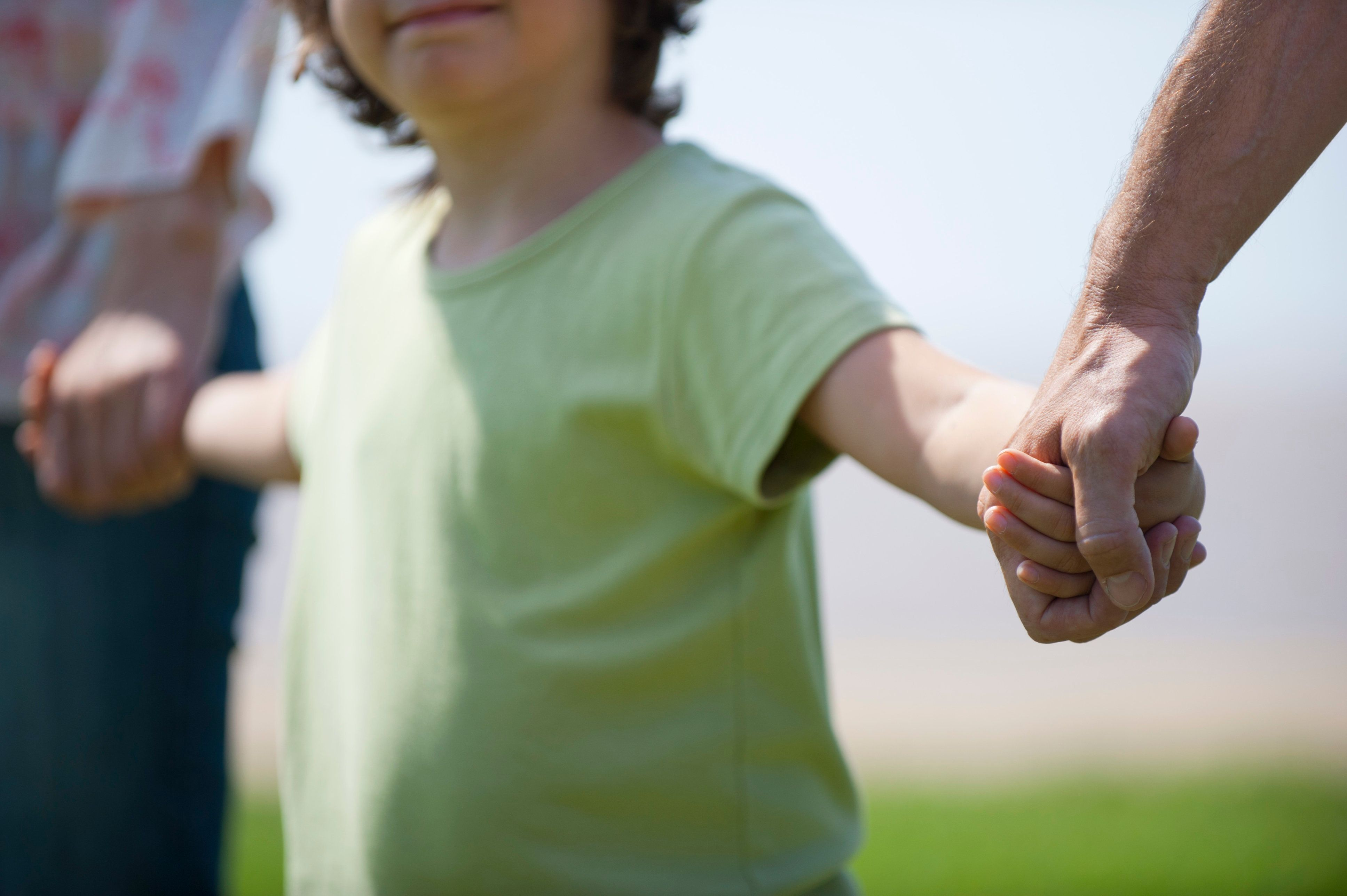 Boy holding hands with parents, cropped