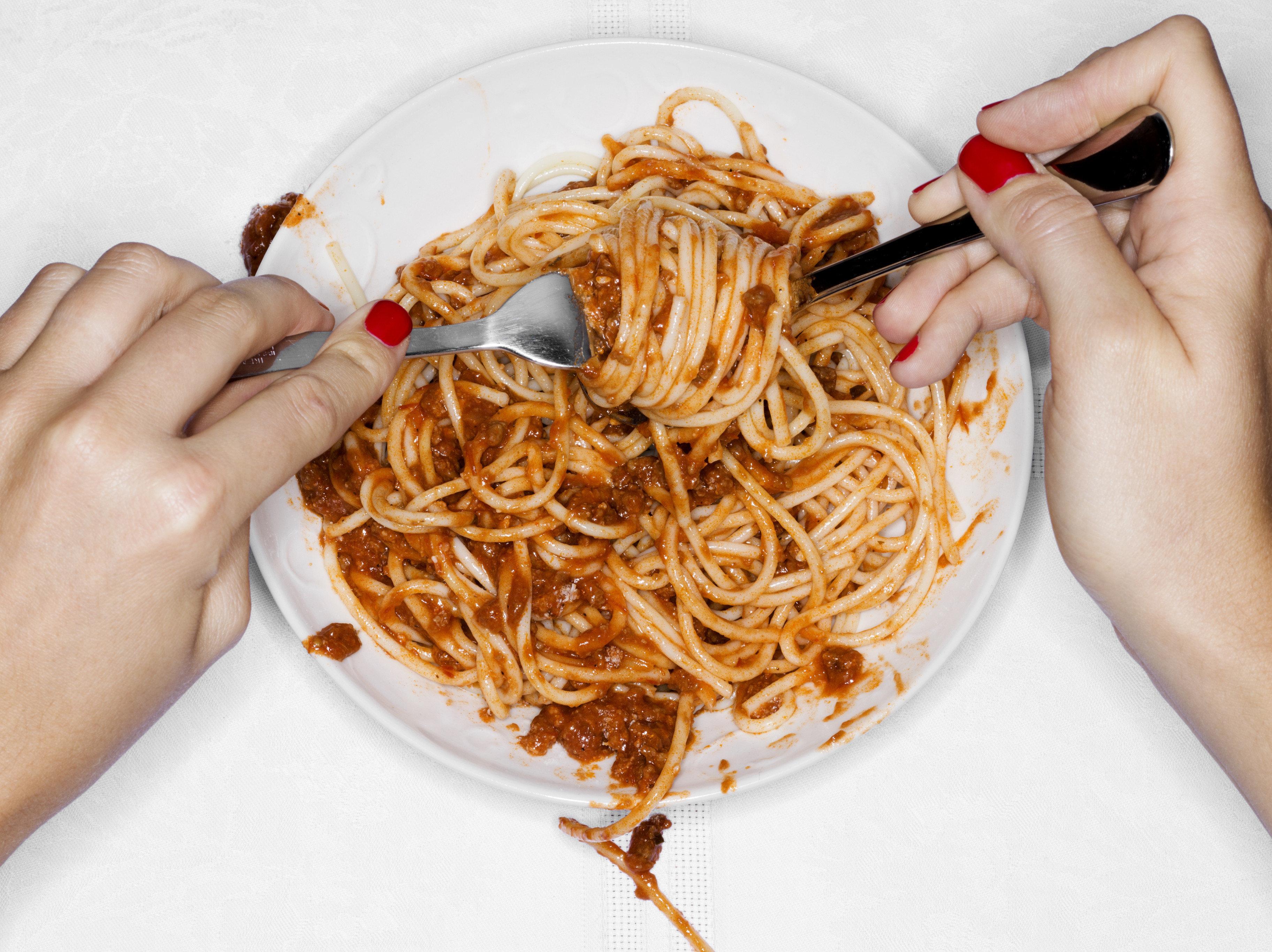 Female eating spaghetti, overhead view