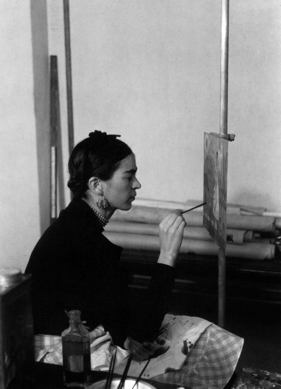 Frida Kahlo painting a self-portrait on the border line between Mexico and United States, for a Detroit Institute of Art mura