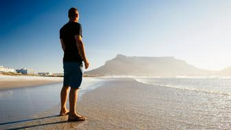 Man standing on beach staring at Table Mountain