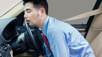 Young businessman driving a car and looks tired, sleeping in the car while wearing the safety belt