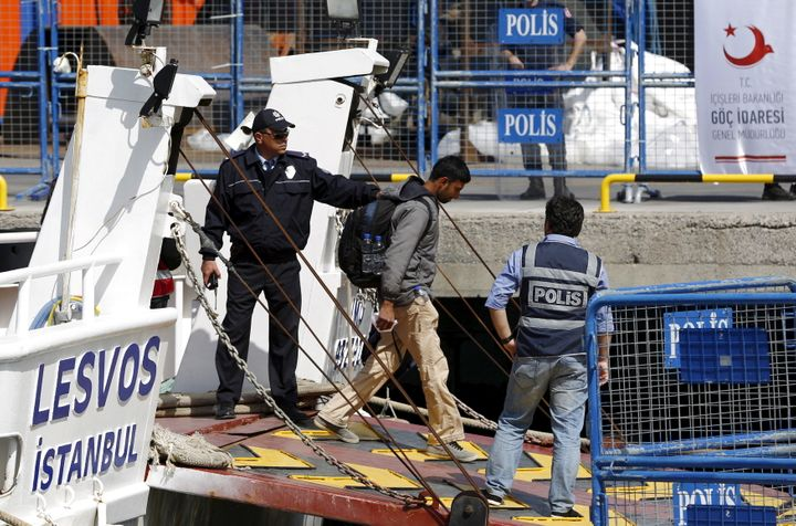 """Police escort a migrant ashore in Dikili, Turkey on April 4, 2016. The UNHCRsaid that Greek police """"forgot"""" to process"""