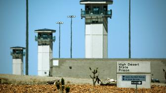 FILE - This April 15, 2015 file photo shows guard towers at High Desert State Prison in Indian Springs, Nev., one of Nevadas toughest prisons. Attorneys for two inmates involved in a deadly prison brawl are accusing prison guards of instigating the fight to set up a gladiator-style contest and then trying to cover it up by blaming the surviving prisoner. (AP Photo/John Locher, File)