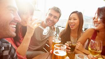 Group Of Friends Enjoying Drink At Outdoor Rooftop Bar Laughing And Chatting Around Table.