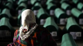 A Bosnian Muslim woman searches for the remains of relatives among 610 recently discovered Bosnian Muslim massacre victims 10 July 2005 in the former battery factory in Potocari near the eastern Bosnian town of Srebrenica. The victims were aged between 14 and 75 years when they were slaughtered by Serb forces under the eyes of United Nations Dutch peacekeepers in July 1995 in the worst massacre in Europe since World War II. The bodies from the most recent mass grave to be excavated will be buried in a memorial cemetery in Potocari on Monday. (Photo credit should read DIMITAR DILKOFF/AFP/Getty Images)