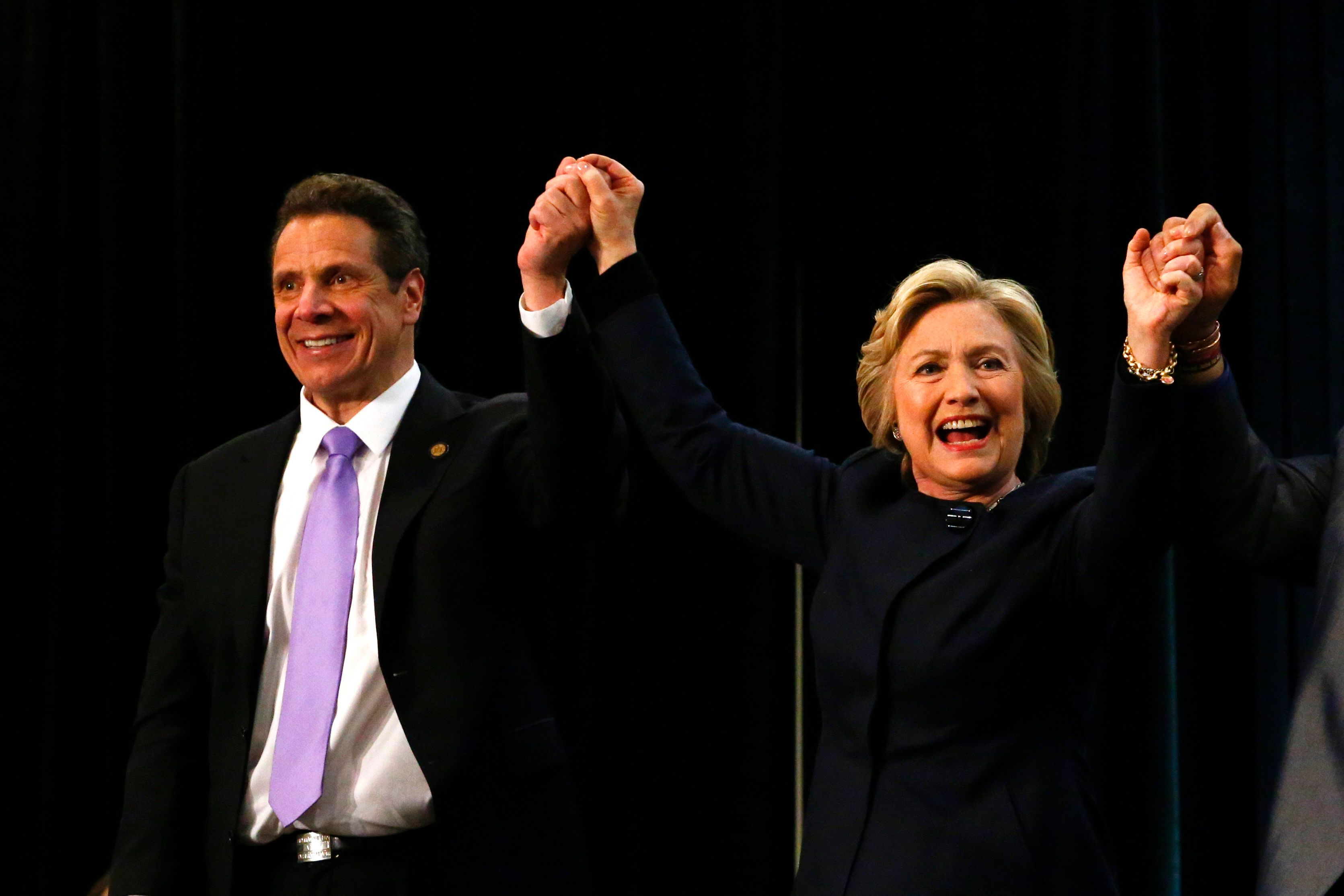 Democratic presidential candidate Hillary Clinton (R) holds the hand of New York Governor Andrew Cuomo during the 'victory rally for $15 minimum wage and paid family leave' at the Javitz Center in New York on April 4,2016.  / AFP / KENA BETANCUR        (Photo credit should read KENA BETANCUR/AFP/Getty Images)