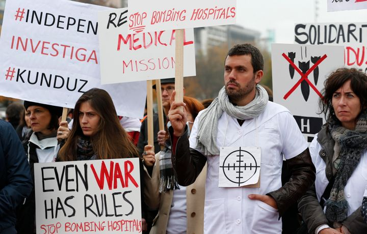 """MSF staff demonstrate in Geneva one month after the bombing of the Kunduz hospital. """"Even war has rules,"""" one of the banner&n"""