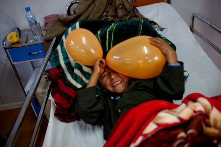 An eight-year-old boy who broke his legplays in his hospital bed in the in-patient ward.