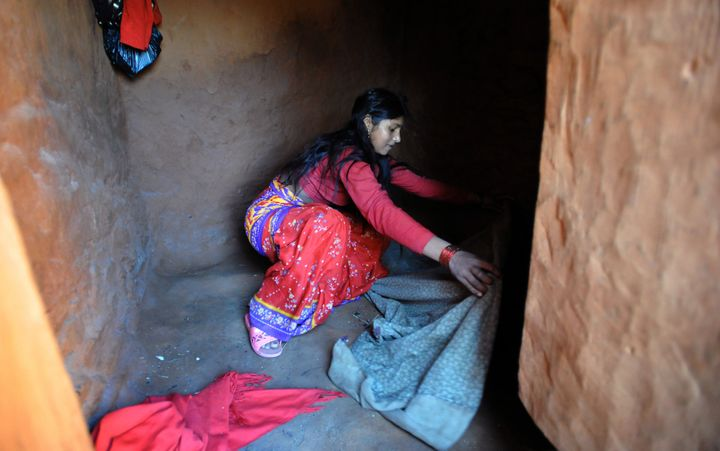 Nepalese villager Chandrakal Nepali prepares her bedding inside a 'chhaupadi house.' Isolation is part of a centuries-old Hin