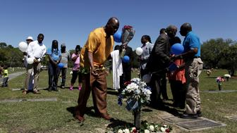 Gary Butts, family friend of the late Walter Scott, lays a rose at the gravesite as relatives and friends gathered to remember Scott, at Live Oak Memorial Gardens in Charleston, South Carolina, April 4, 2016. REUTERS/Randal Hill