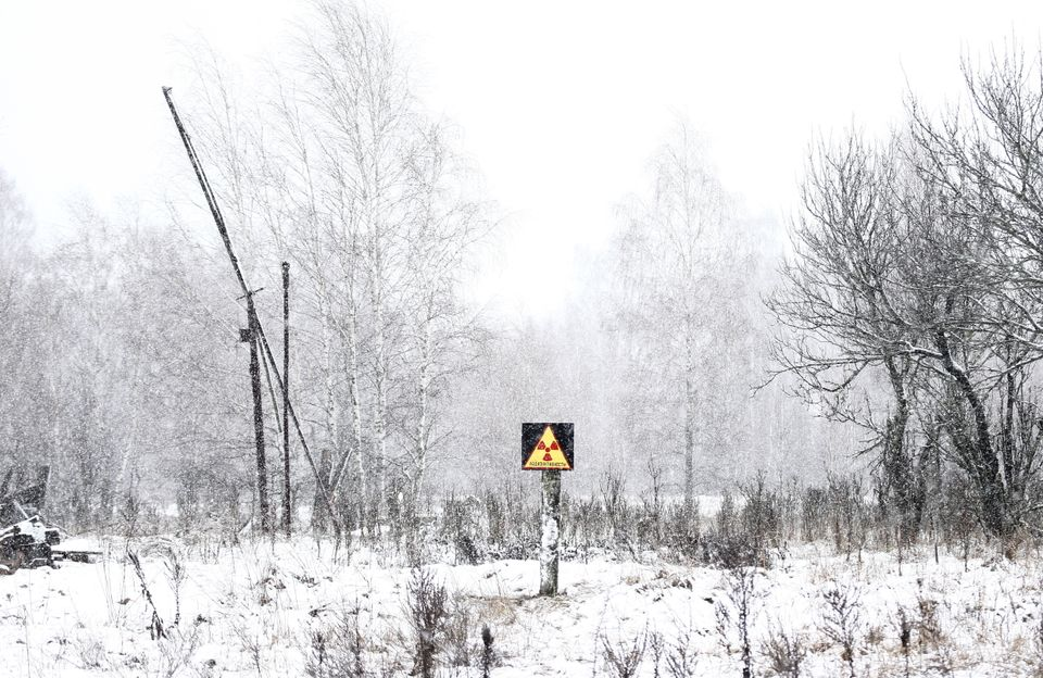 A radiation sign is posted in a field near the exclusion zone.