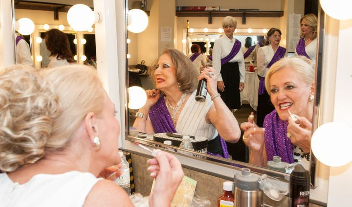 Two contestants work on their hair and makeup backstage.