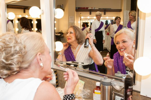 The contestants work on their hair and makeup backstage.