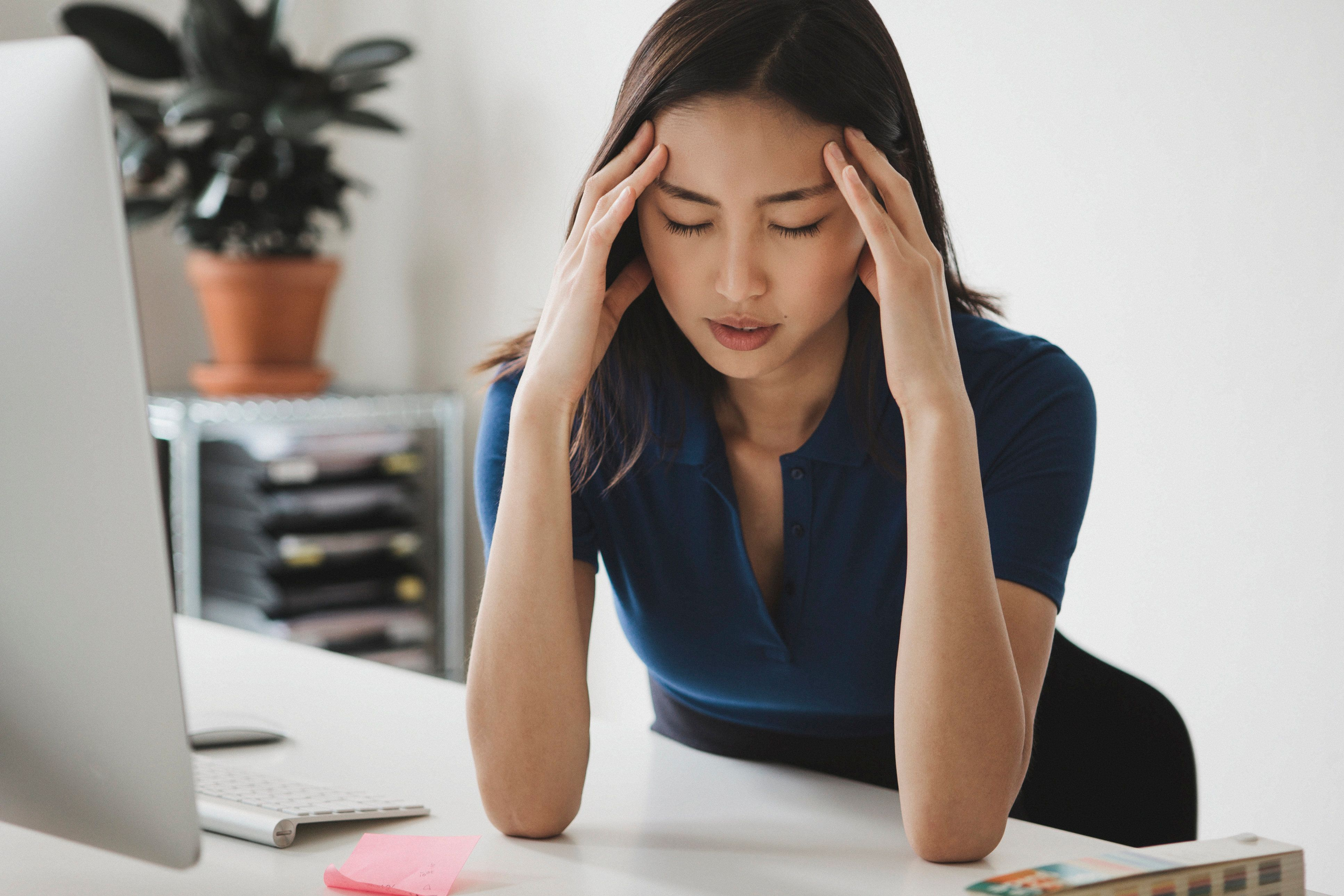 Young businesswoman suffering from headache at desk in office