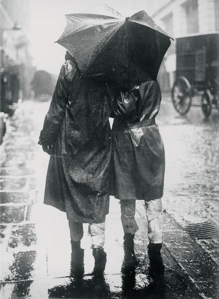 A couple stays dry during a 1930s storm wearing Mackintosh jackets around their backs and newsprint around their legs.