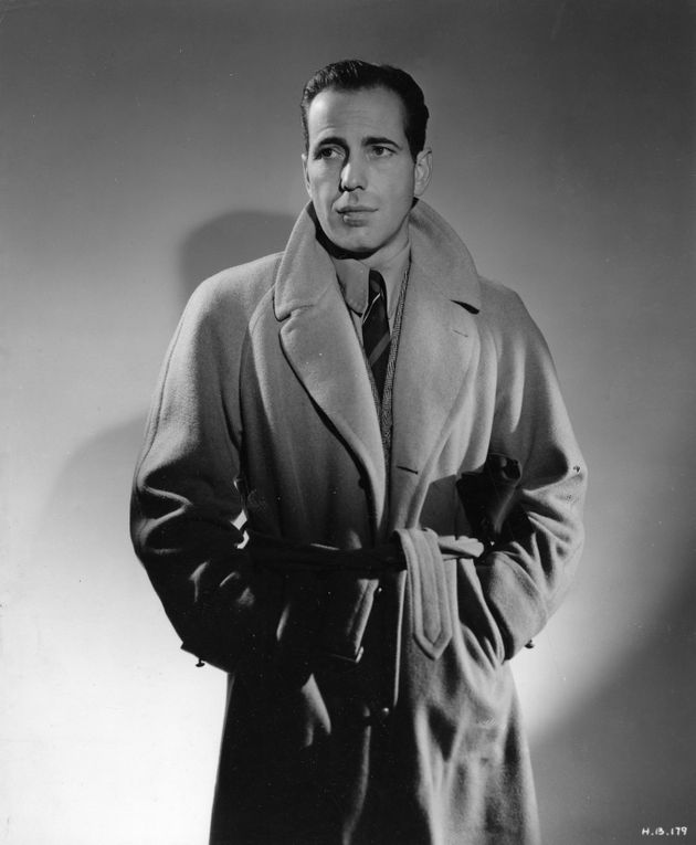 Humphrey Bogart, one of the trench coat's most famous wearers, sports it here in a publicity shot circa