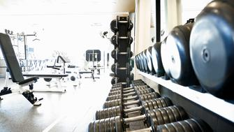 Row of free weights in foreground and exercise machines in background of an empty health club