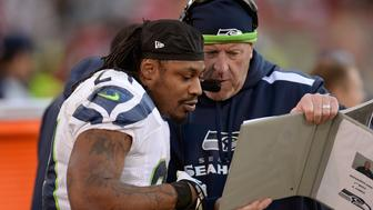 SAN FRANCISCO, CA - DECEMBER 08:  Marshawn Lynch #24 of the Seattle Seahawks looks over plays with Assistan Head Coach Tom Cable on the sideline during the fourth quarter against the San Francisco 49ers at Candlestick Park on December 8, 2013 in San Francisco, California.  (Photo by Thearon W. Henderson/Getty Images)