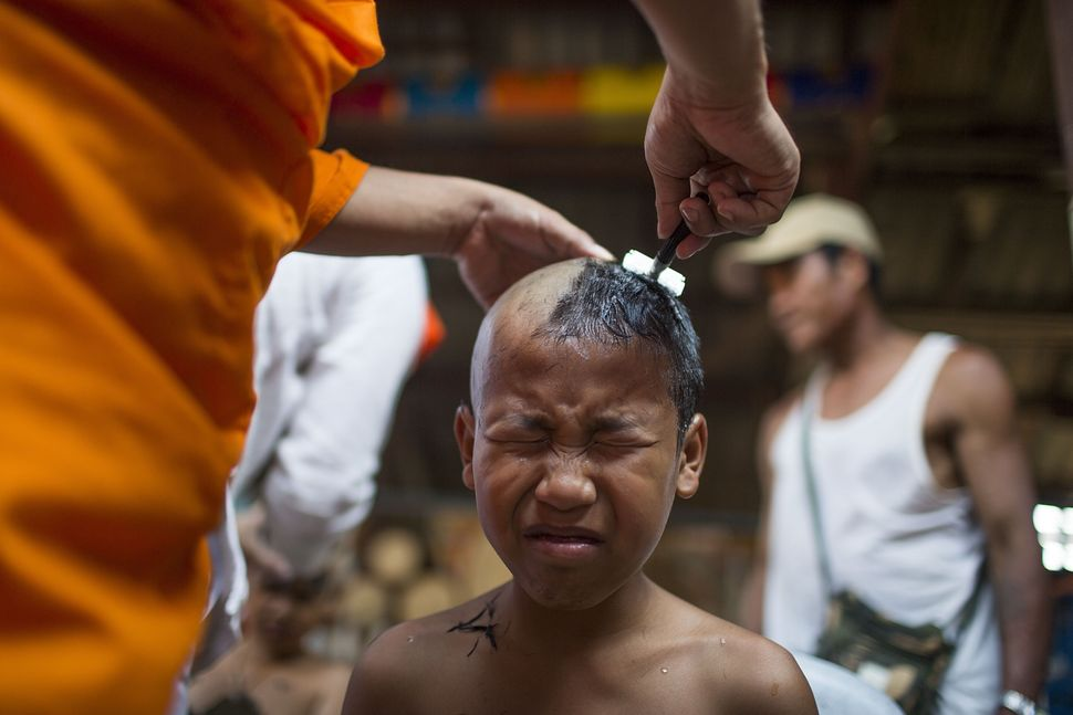 Kemachart grimaces as a monk shaves his head.