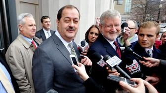 Former Massey Energy Chief Executive Don Blankenship (3rd L) and his attorney Bill Taylor (4th R) are met by media outside the Robert C. Byrd U.S. Courthouse in Charleston, West Virginia December 3, 2015. Blankenship was found guilty in federal court on Thursday of conspiring to violate safety standards at the Upper Big Branch mine, the site of a 2010 blast that killed 29 people.    REUTERS/Chris Tilley