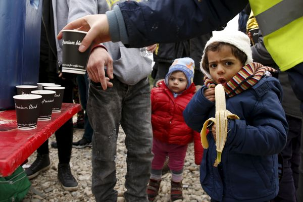 A child eats a banana as hot drinks are distributed moments after the arrival of a rubber dinghy on Lesbos, on Jan. 29, 2016.