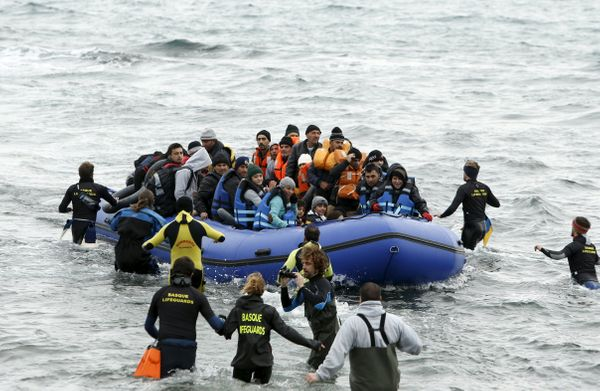 Volunteers approach a rubber dinghy packed with migrants and refugees as it arrives on Lesbos on Jan. 29, 2016.