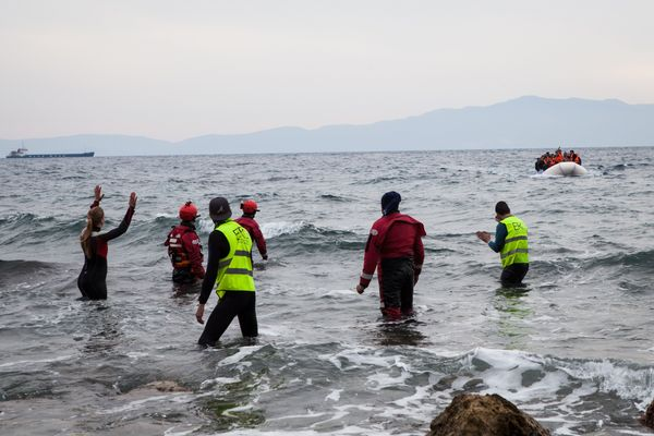 People hail a dinghy as it arrives to Lesbos on March 22, 2016.