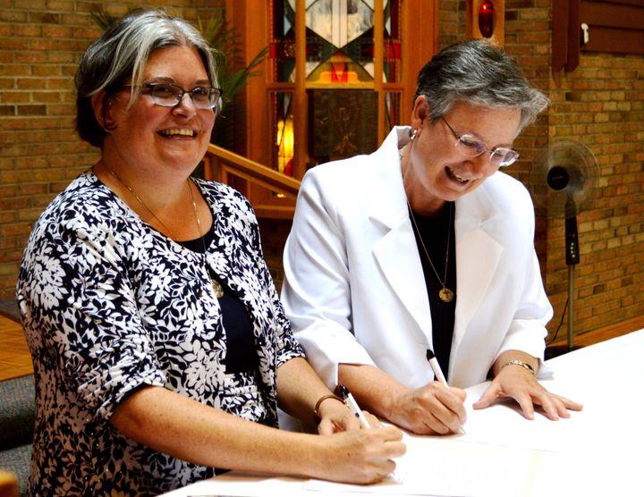 Sister Jennifer Wilson (left) signs her final vows.