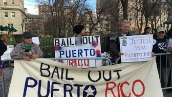 Activists protest at a Federal Reserve event in Manhattan, asking for relief for Puerto Rico's debt.