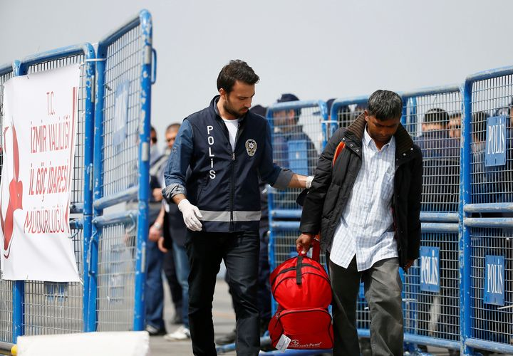 More than 120 migrants and refugees were returned to Turkey from the Greek island of Lesbos on Friday. Police escort a migran