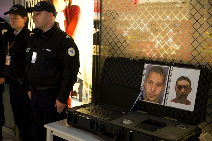 Police officers stand next to the wanted notice of Abrini (R) and Abdeslam, who was arrested on March 18 in Brussels, four da