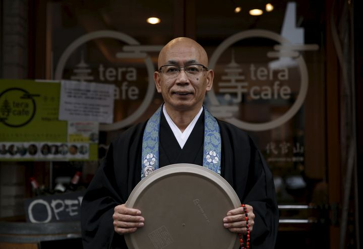 Shokyo Miura, a Buddhist monk and one of the on-site priests, poses for pictures outside Tera Cafe in Tokyo, Japan, April 1,