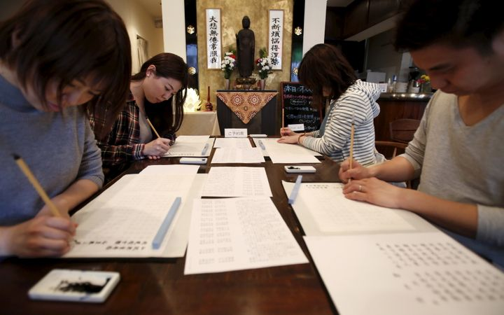 People trace Buddhist sutras with brushes at Tera Cafe in Tokyo, Japan, April 1, 2016.