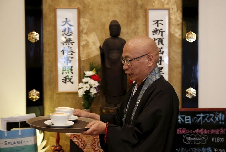Shokyo Miura, a Buddhist monk and one of the on-site priests, carries cups of coffee past a statue of Buddha at Tera Cafe in