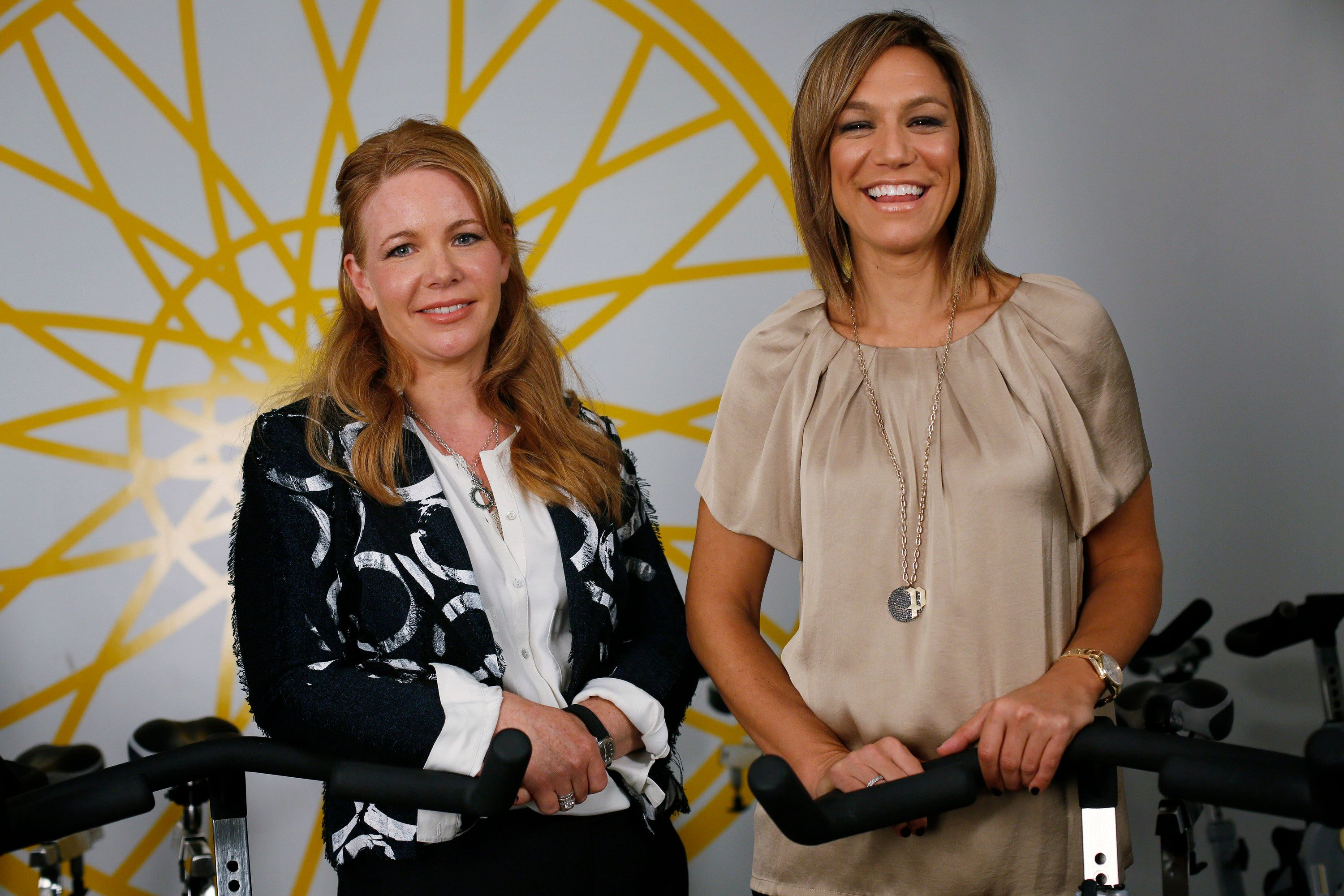 Elizabeth Cutler, left, and Julie Rice, right, co-founders of SoulCycle LLC, stand for a photo at a Soul Cycle studio in New York, U.S., on Tuesday, Oct. 2, 2012. SoulCycle offers an indoor cycling program that has riders work their core and use hand weights to achieve a full body workout. Photographer: Victor J. Blue/Bloomberg via Getty Images