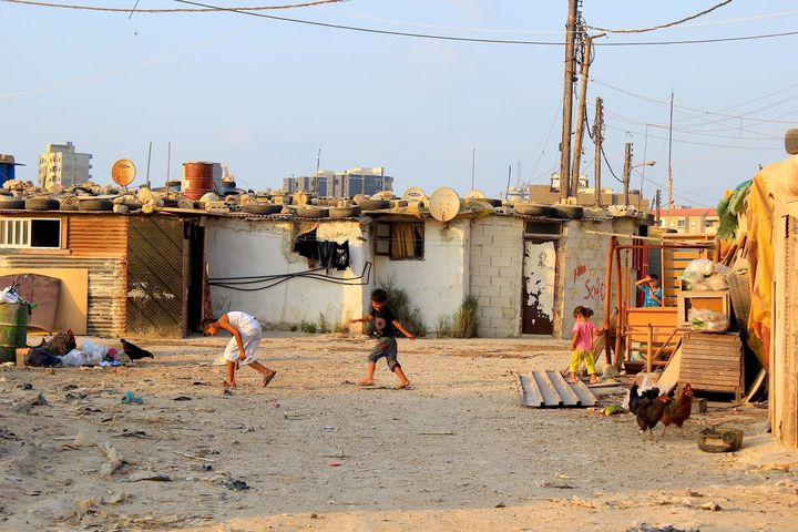 Syrian refugee children play outside a slum complex in Tripoli.