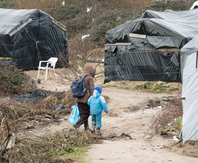 A woman walks with her child in the Calais