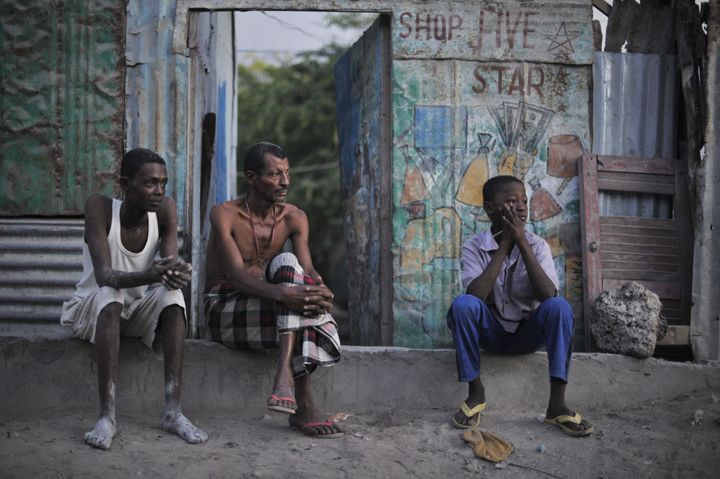 A father and his two sons watch a security operation in Mogadishu in 2013. Somalia will hold elections, but not by popular vo