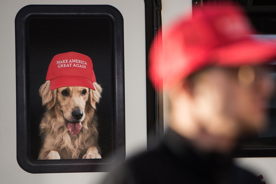 A man stands near a Donald Trump campaign vehicle with an image of a dog in a window before a campaign rally on Feb. 5, 2016,