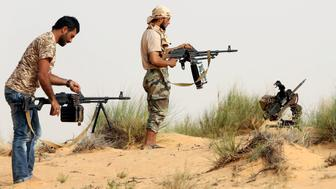 Fighters from the Fajr Libya (Libya Dawn) militia load their weapons during clashes with forces loyal to Libya's internationally recognised government, southwest of Sabratha, in the vicinity of the Wetia military air base, some 87 kilometres west of the capital Tripoli,  on May 25, 2015. AFP PHOTO / MAHMUD TURKIA        (Photo credit should read MAHMUD TURKIA/AFP/Getty Images)