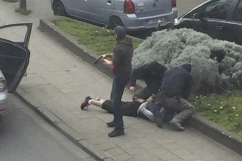 Police officers detain a suspect during a raid in which Mohamed Abrini was arrested in Anderlecht, near Brussels. Police raid